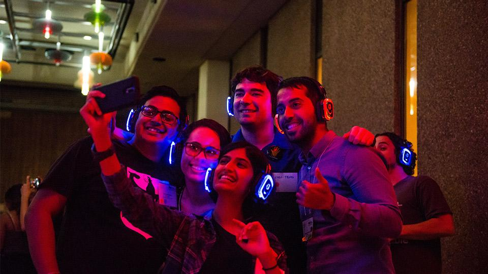 Students with headphones on posing for a group photo.