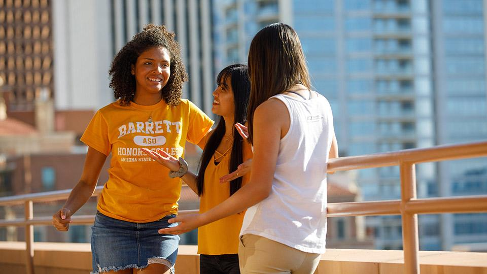Three students smiling and chatting near a railing.