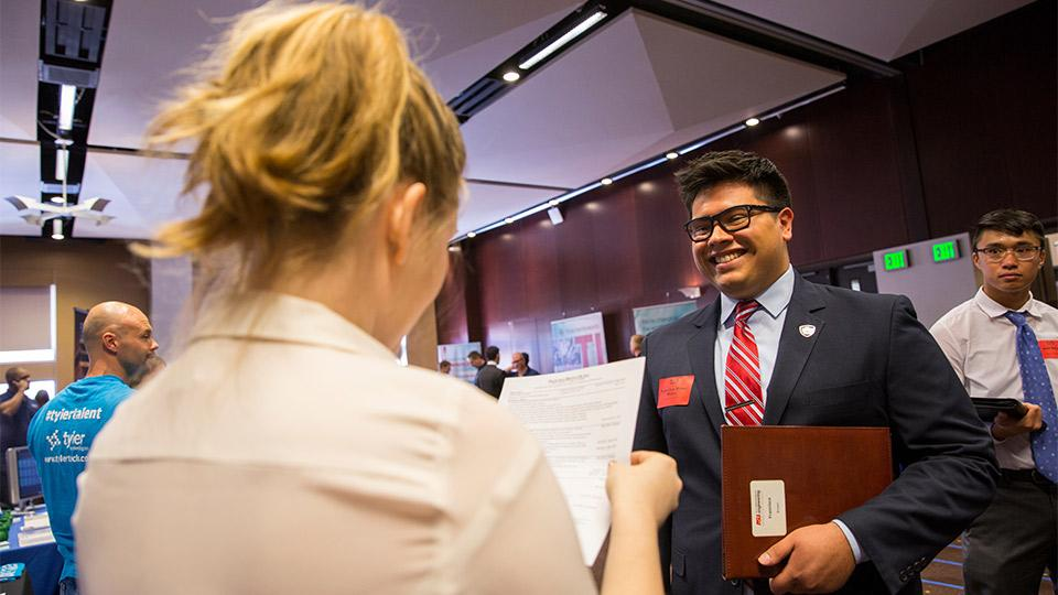 Man networking with an employer at a career fair.