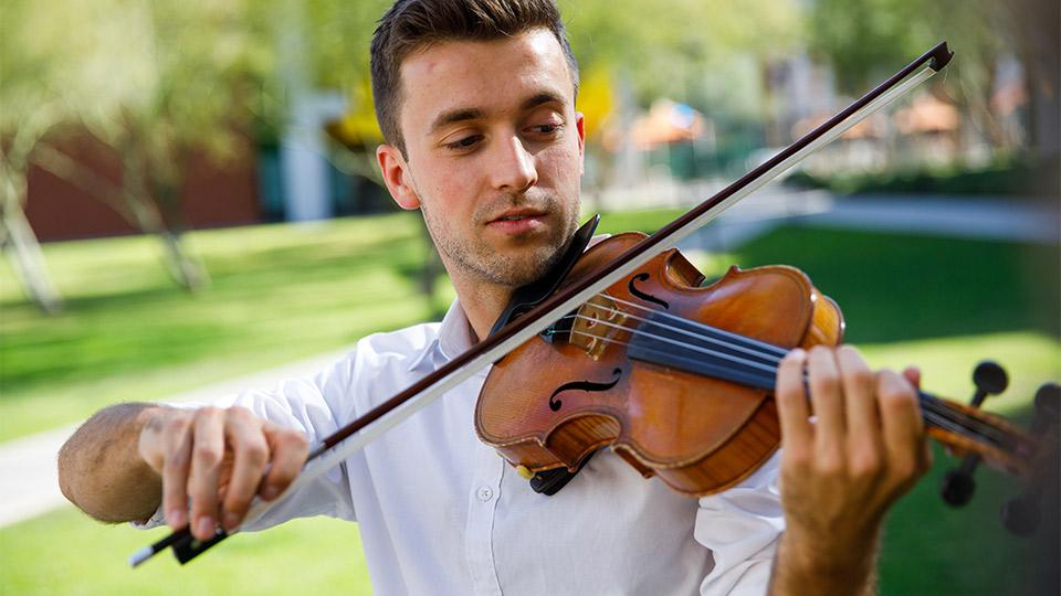 A man playing a violin outdoors.